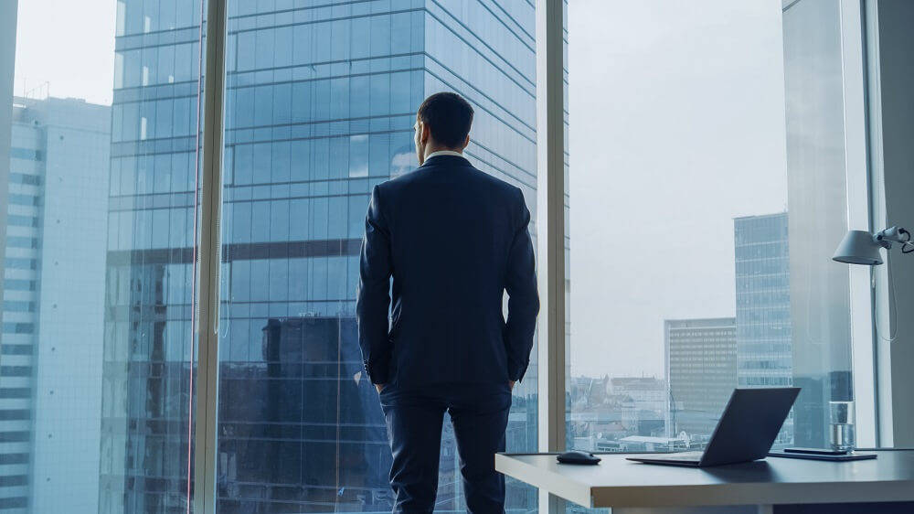 man in suit standing next to large window from an office building looking contemplative