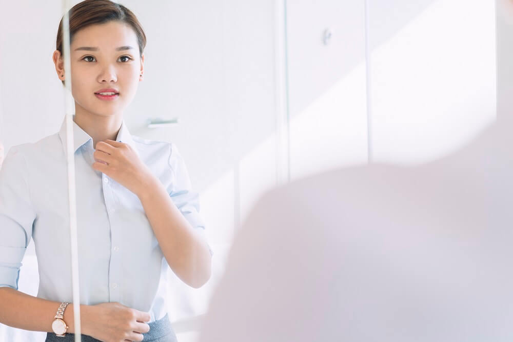 east asian woman with brown hair in a bun looking into a mirror and buttoning her shirt preparing for an interview