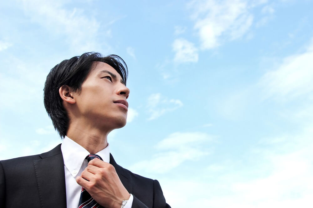 young man in a suit and tie looking hopefully at a blue sky