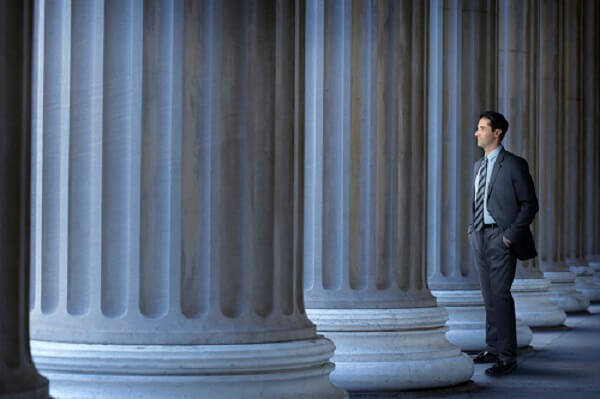 Man in blue suit between columns