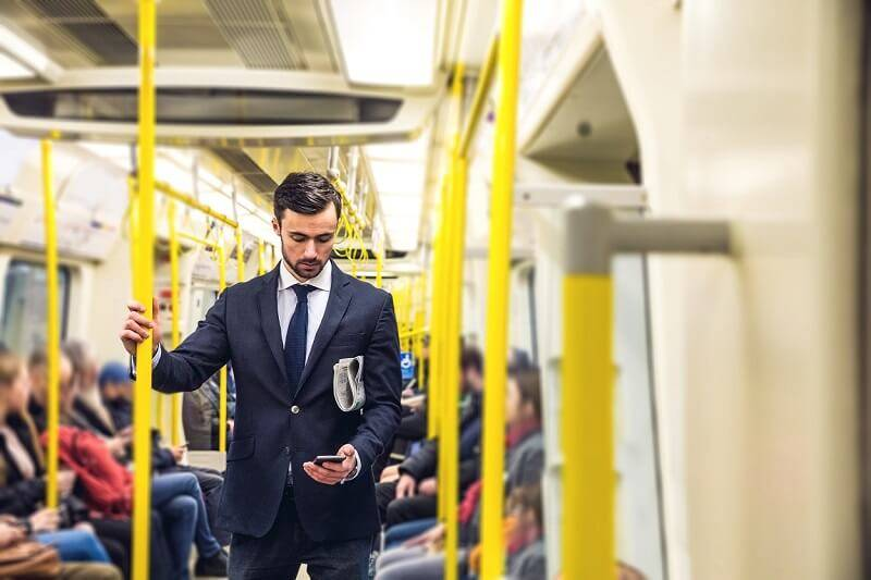 Interim lawyer commuting to work on the tube in a suit