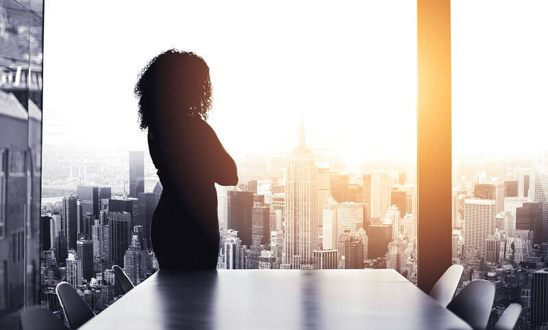 female lawyer standing in a boardroom overlooking a city skyline with arms crossed in silhouette