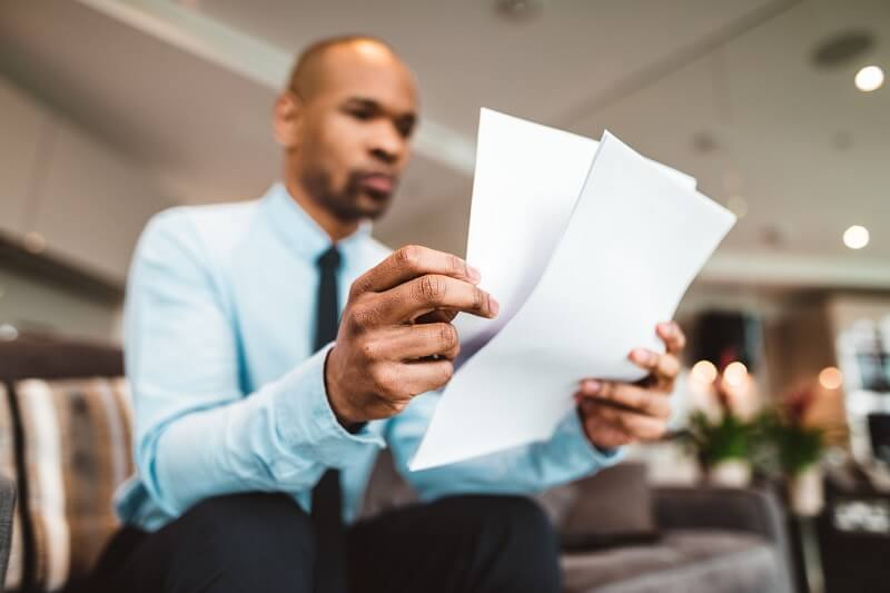 man reading legal papers in an office