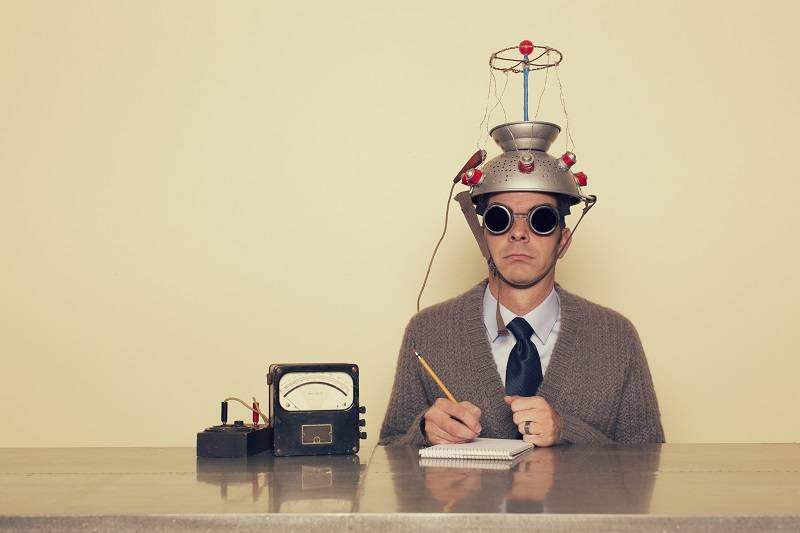 man sitting at a desk with a funny contraption on his head and a pencil in his hands