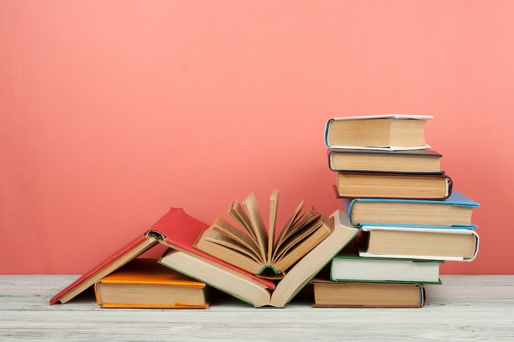 Stack of school books against a pink wall as blog header image