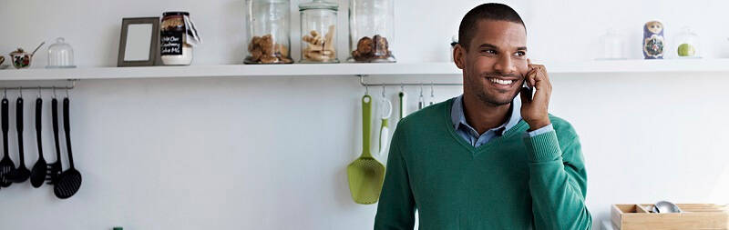 smiling man in his kitchen talking on the phone in a green jumper