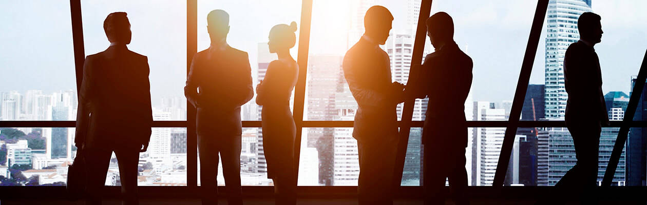 group of lawyers in silhouette in front of a a glass wall
