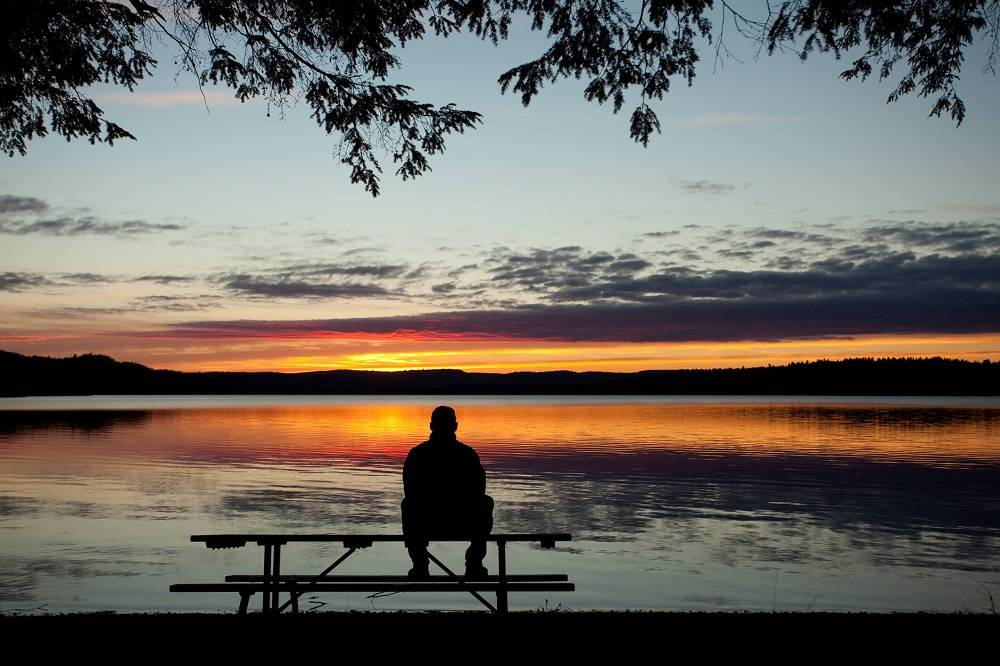 silhouetted man sitting on a bench at sunset staring at the sky