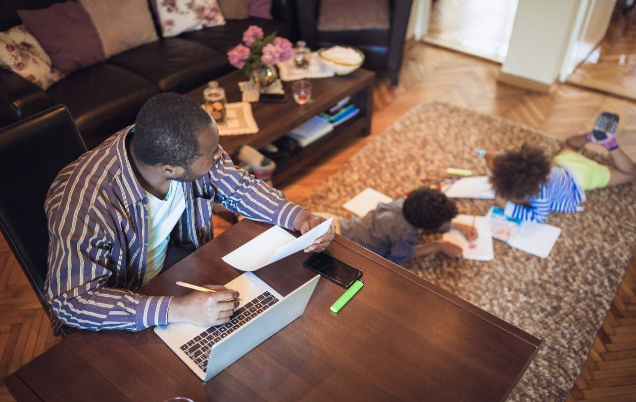 man working from home while looking after his children